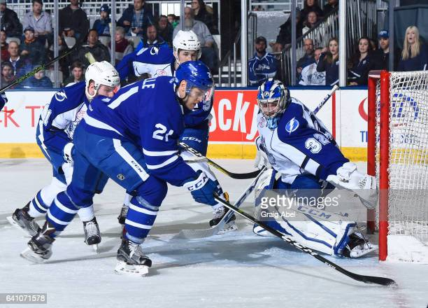 Eric Faille of the Toronto Marlies tries to throw the puck past Adam Wilcox the Syracuse Crunch while Tanner Richard and Jonathan Racine of the...