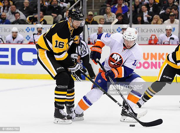 Eric Fehr of the Pittsburgh Penguins skates with the puck as Josh Bailey of the New York Islanders tries to poke the puck away at PPG PAINTS Arena on...