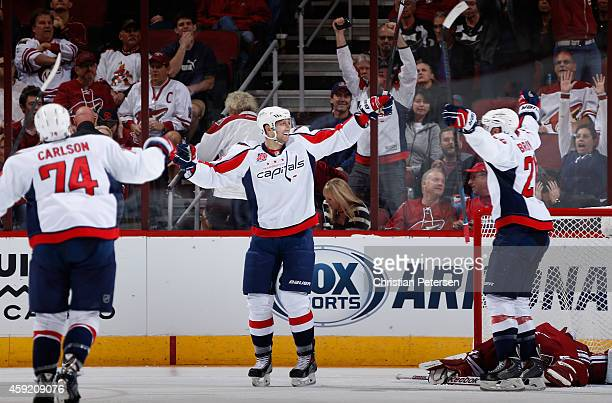 Eric Fehr of the Washington Capitals celebrates with John Carlson and Troy Brouwer after scoring the game winning overtime goal past goaltender Mike...