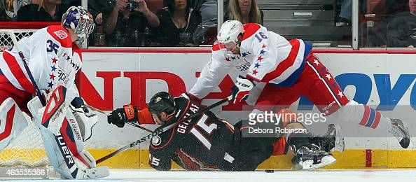 Eric Fehr of the Washington Capitals knocks Ryan Getzlaf of the Anaheim Ducks to the ice with goalie Justin Peters protecting his goal on February 15...