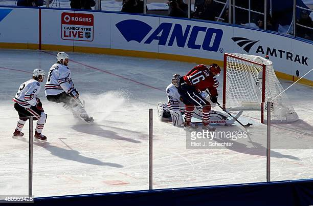 Eric Fehr of the Washington Capitals slides a shot past goaltender Corey Crawford of the Chicago Blackhawks in the first period during the 2015...