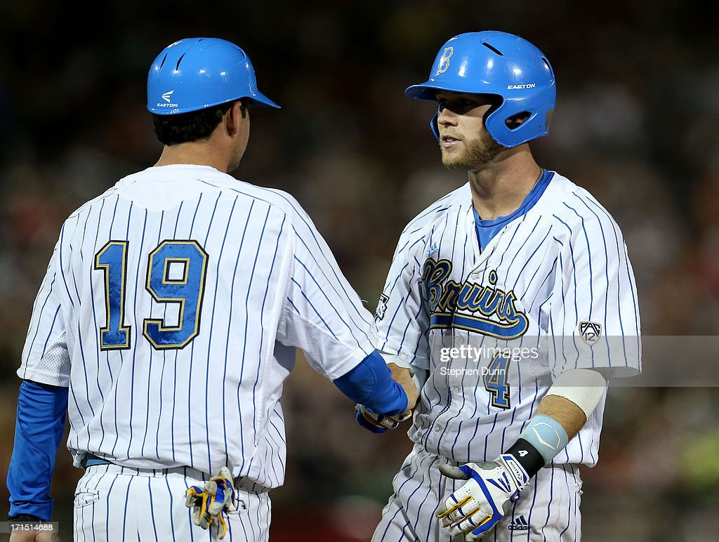 Eric Filia #4 of the UCLA Bruins is congratulated by first base coach Jake Silverman after picking up his third RBI of the game with a one run sngle in the sixth inning against the Mississippi State Bulldogs during game two of the College World Series Finals on June 25, 2013 at TD Ameritrade Park in Omaha, Nebraska.