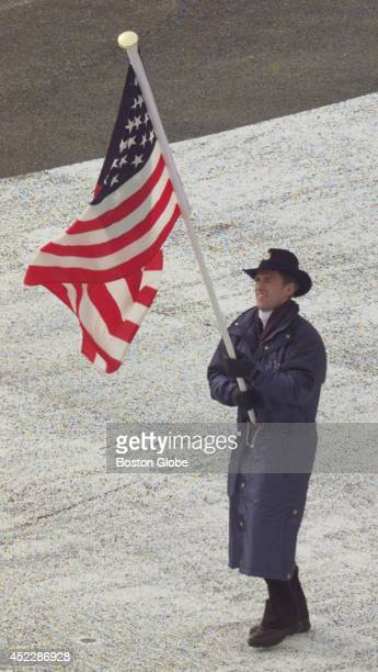Eric Flaim carries the flag into Olympic Stadium ahead of the US team
