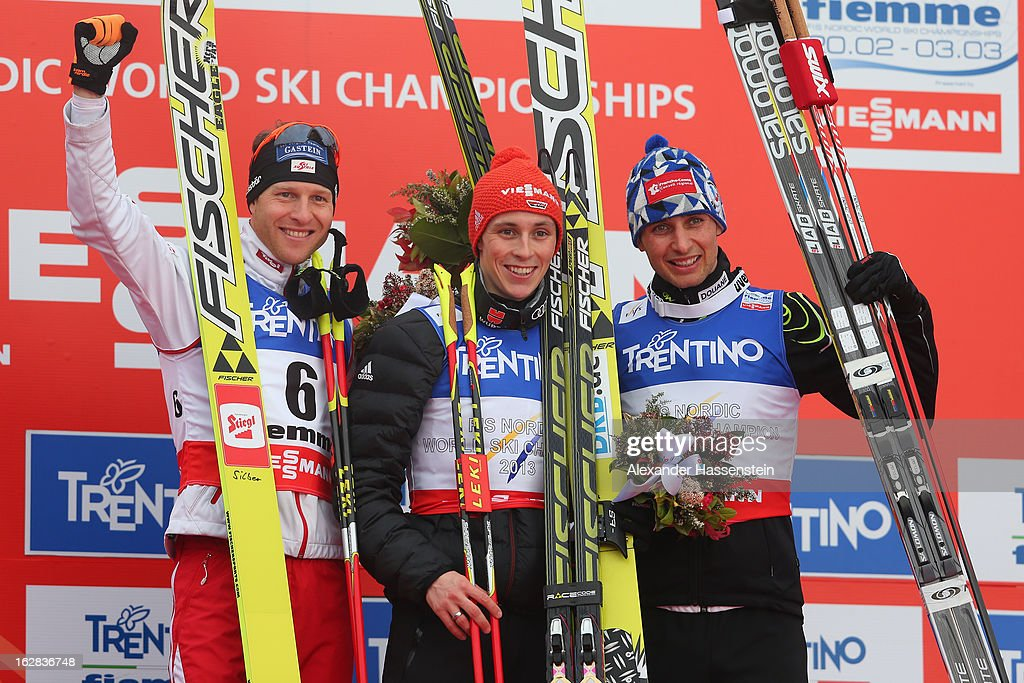Eric Frenzel of Germany celebrates victory in the Men's Nordic Combined on the podium with second placed Bernhard Gruber of Austria (l) and third placed Jason Lamy Chappuis of France (r) following the Individual Gundersen 10Km at the FIS Nordic World Ski Championships on February 28, 2013 in Val di Fiemme, Italy.