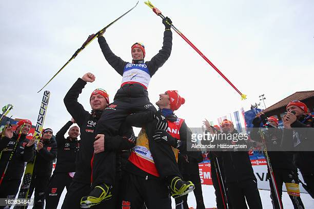 Eric Frenzel of Germany celebrates victory in the Men's Nordic Combined with his teammates following the Individual Gundersen 10Km at the FIS Nordic...