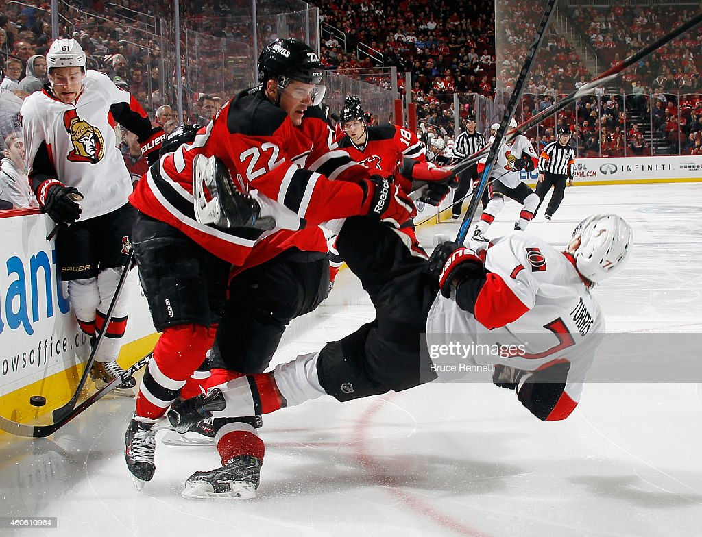 Eric Gelinas of the New Jersey Devils checks Kyle Turris of the Ottawa Senators during the third period at the Prudential Center on December 17 2014...