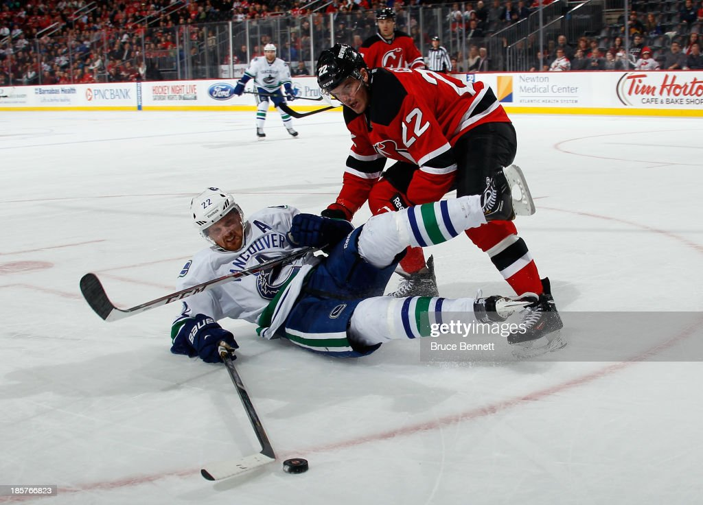 Eric Gelinas #22 of the New Jersey Devils dumps <a gi-track='captionPersonalityLinkClicked' href=/galleries/search?phrase=Daniel+Sedin&family=editorial&specificpeople=202492 ng-click='$event.stopPropagation()'>Daniel Sedin</a> #22 of the Vancouver Canucks during the third period at the Prudential Center on October 24, 2013 in Newark, New Jersey. The Canucks defeated the Devils 3-2 in the shootout.