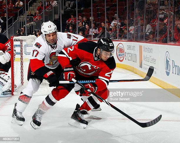 Eric Gelinas of the New Jersey Devils is checked by David Legwand of the Ottawa Senators during the first period at the Prudential Center on December...