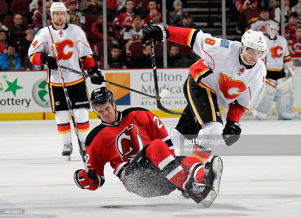 Eric Gelinas #22 of the New Jersey Devils is hit by <a gi-track='captionPersonalityLinkClicked' href=/galleries/search?phrase=Joe+Colborne&family=editorial&specificpeople=5370968 ng-click='$event.stopPropagation()'>Joe Colborne</a> #8 of the Calgary Flames during the third period at the Prudential Center on April 7, 2014 in Newark, New Jersey. The Flames shutout the Devils 1-0.