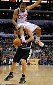 Eric Gordon of the Los Angeles Clippers lands on Manu Ginobili of the San Antonio Spurs attempting to block his shot during the game at Staples...