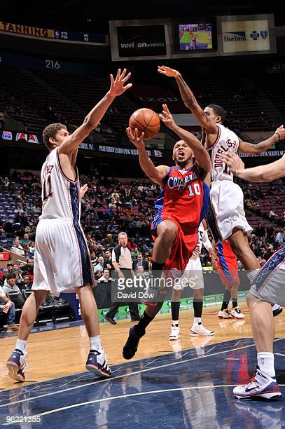 Eric Gordon of the Los Angeles Clippers shoots against Brook Lopez and Chris DouglasRoberts of the New Jersey Nets during the game on January 27 2010...