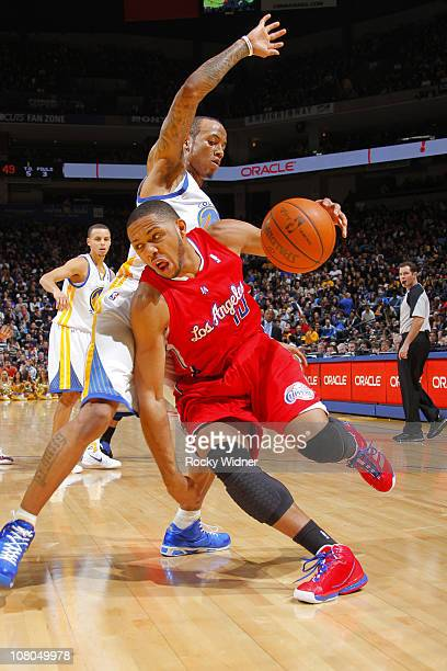 Eric Gordon of the Los Angeles Clippers slashes to the hoop against Monta Ellis of the Golden State Warriors on January 14 2011 at Oracle Arena in...