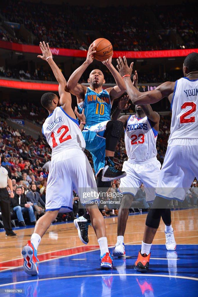 Eric Gordon #10 of the New Orleans Hornets drives to the basket against Evan Turner #12 and Jason Richardson #23 of the Philadelphia 76ers during the game at the Wells Fargo Center on January 15, 2013 in Philadelphia, Pennsylvania.
