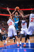 Eric Gordon of the New Orleans Hornets drives to the basket against Evan Turner and Jason Richardson of the Philadelphia 76ers during the game at the...