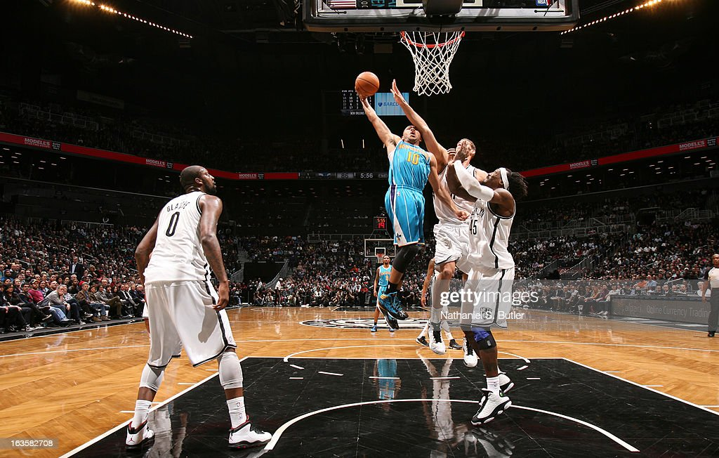Eric Gordon #10 of the New Orleans Hornets dunks against Brook Lopez #11 and Gerald Wallace #45 of the Brooklyn Nets on March 12, 2013 at the Barclays Center in the Brooklyn borough of New York City.
