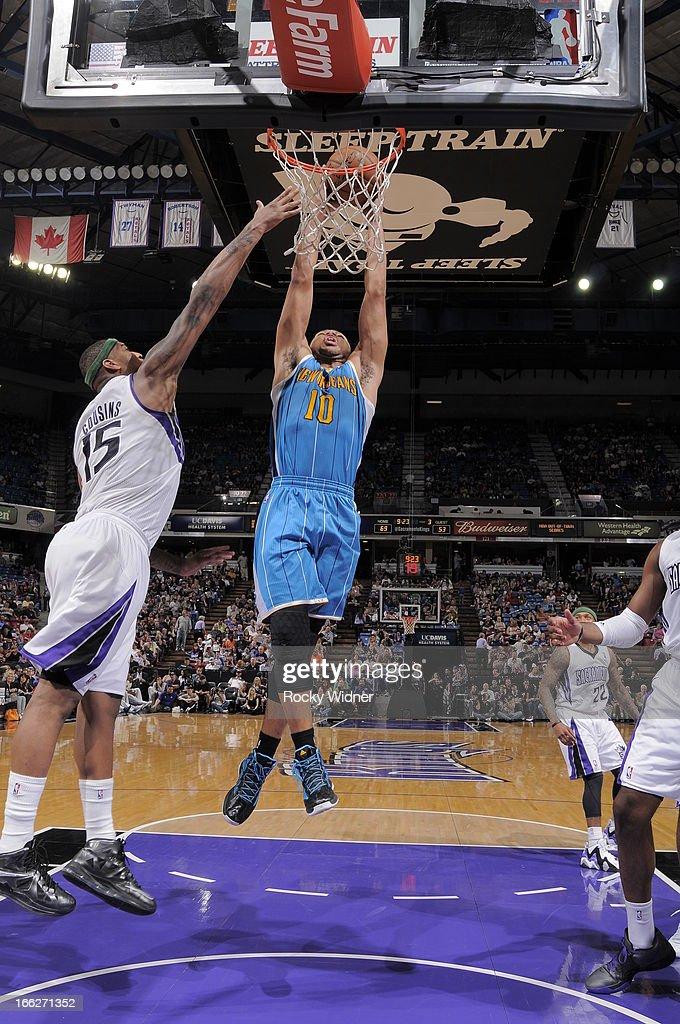 Eric Gordon #10 of the New Orleans Hornets dunks the ball against DeMarcus Cousins #15 of the Sacramento Kings on April 10, 2013 at Sleep Train Arena in Sacramento, California.