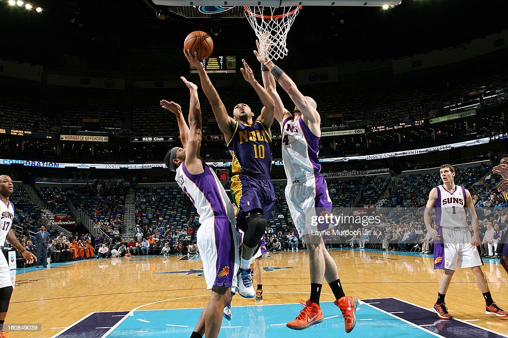 Eric Gordon #10 of the New Orleans Hornets goes to the basket against Jared Dudley #3 and Marcin Gortat #4 of the Phoenix Suns on February 06, 2013 at the New Orleans Arena in New Orleans, Louisiana.