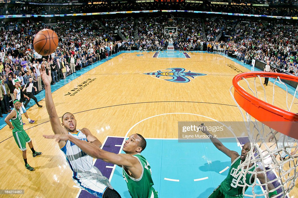Eric Gordon #10 of the New Orleans Hornets misses a shot in the lane against Avery Bradley #0 of the Boston Celtics, resulting in a game-winning tip by teammate Anthony Davis #23, on March 20, 2013 at the New Orleans Arena in New Orleans, Louisiana.