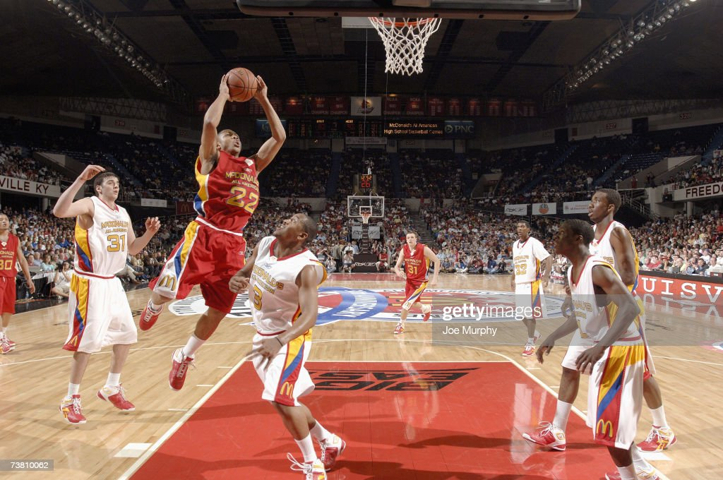 Eric Gordon of the West Team goes to the basket against Kosta Koufos and Austin Freeman of the East Team during the Boy's McDonald's All American...