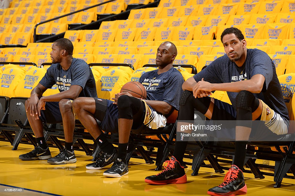 Eric Gordon Quincy Pondexter and Alexis Ajinca of the New Orleans Pelicans sit on the bench before Game Two of the Western Conference Quarterfinals...