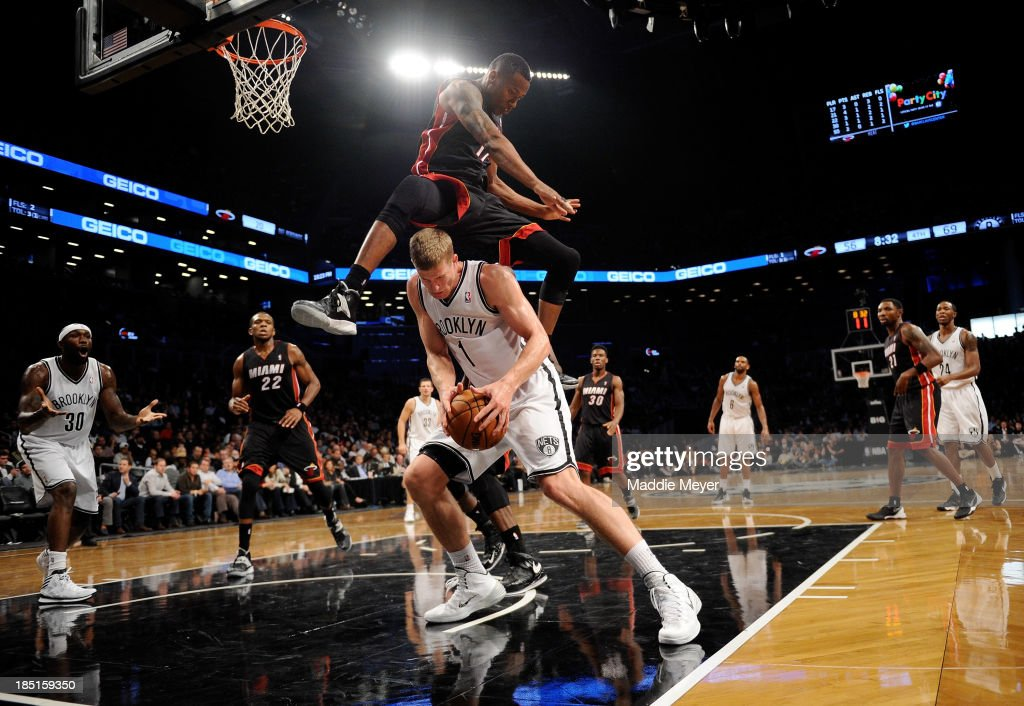 Eric Griffin #17 of the Miami Heat jumps over Mason Plumlee #1 of the Brooklyn Nets during the fourth quarter at Barclays Center on October 17, 2013 in the Brooklyn borough of New York City.