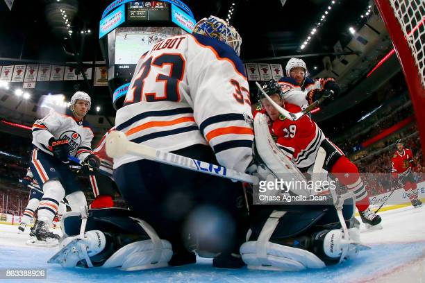 Eric Gryba of the Edmonton Oilers reaches over Jonathan Toews of the Chicago Blackhawks as he works to get the puck next to goalie Cam Talbot at the...