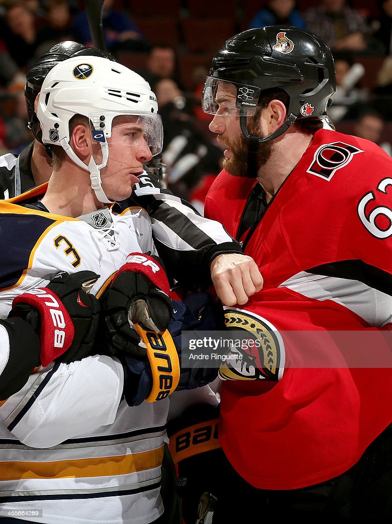 <a gi-track='captionPersonalityLinkClicked' href=/galleries/search?phrase=Eric+Gryba&family=editorial&specificpeople=570539 ng-click='$event.stopPropagation()'>Eric Gryba</a> #62 of the Ottawa Senators and <a gi-track='captionPersonalityLinkClicked' href=/galleries/search?phrase=Mark+Pysyk&family=editorial&specificpeople=6571526 ng-click='$event.stopPropagation()'>Mark Pysyk</a> #3 of the Buffalo Sabres stare each other down in a scrum at Canadian Tire Centre on December 12, 2013 in Ottawa, Ontario, Canada.