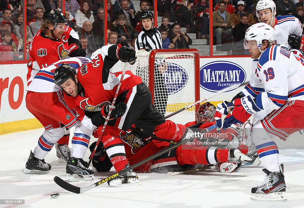 Eric Gryba #62 of the Ottawa Senators falls to the ice as he attempts to clear the puck away from Brad Richards #19 of the New York Rangers, during an NHL game at Scotiabank Place on February 21, 2013 in Ottawa, Ontario, Canada.