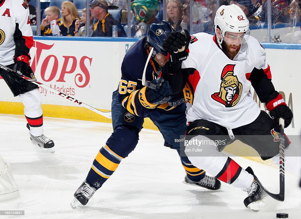 Eric Gryba #62 of the Ottawa Senators tries to control the puck while battling with Brian Flynn #65 of the Buffalo Sabres at First Niagara Center on October 4, 2013 in Buffalo, New York.