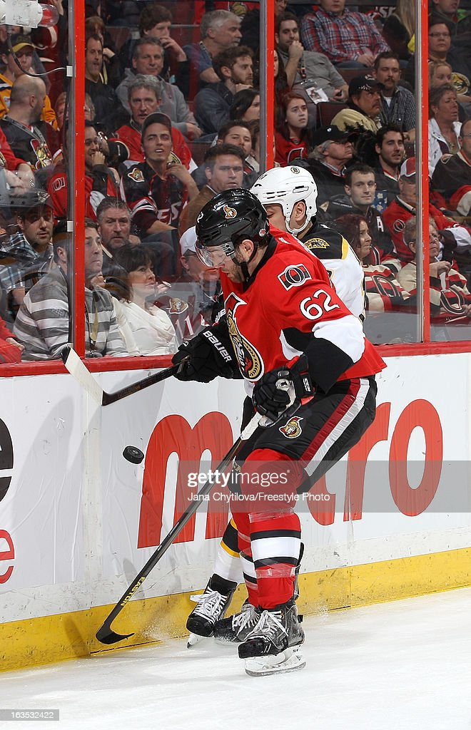 Eric Gryba #62 of the Ottawa Senators uses his body to block Milan Lucic #17 of the Boston Bruins from the puck, during an NHL game at Scotiabank Place, on March 11, 2013 in Ottawa, Ontario, Canada.