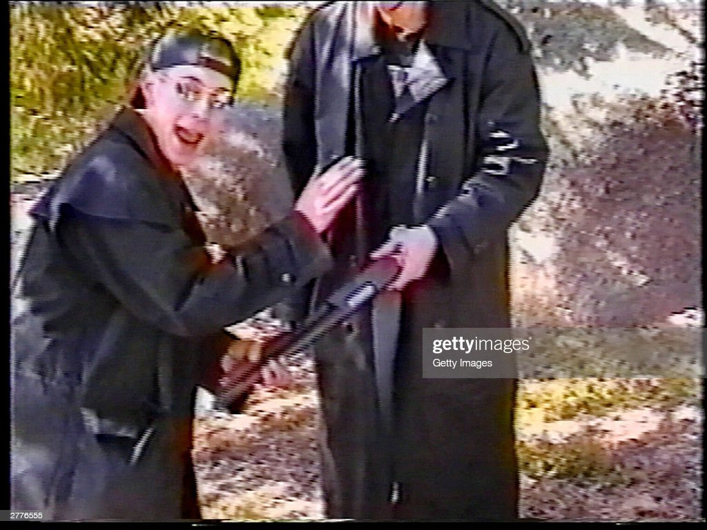 Eric Harris points out a sawedoff shotgun held by friend Dylan Klebold at a makeshift shooting range March 6 1999 in Douglas County CO in this image...