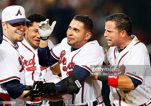 Eric Hinske and Martin Prado of the Atlanta Braves celebrate with Omar Infante after Infante's tworun single in the 11th inning to give the Braves a...