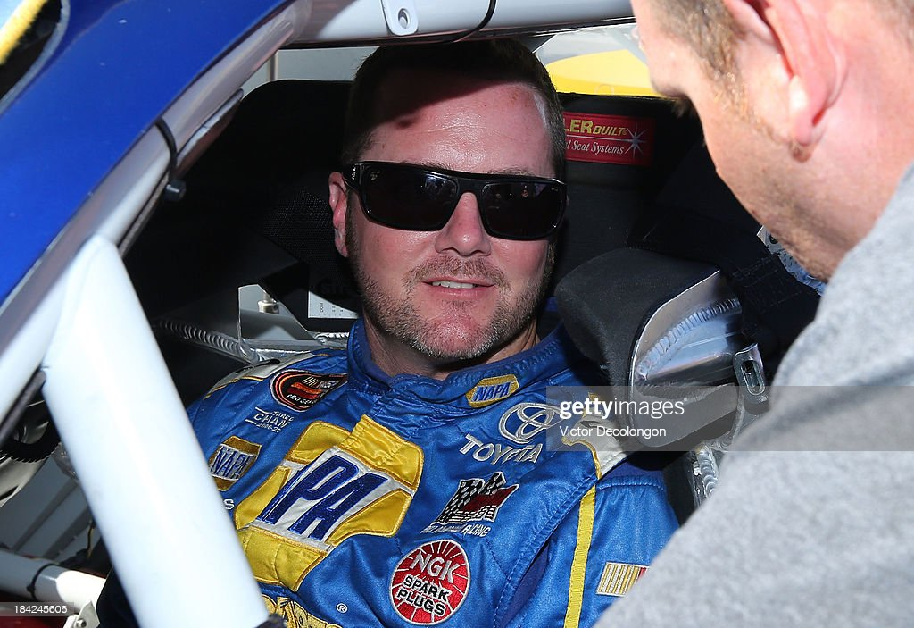 Eric Holmes, driver of the #16 NAPA Auto Parts Toyota, talks with one of his crew members during the final practice prior to the NASCAR K&N Toyota/NAPA Auto Parts 150 at All American Speedway on October 12, 2013 in Roseville, California.