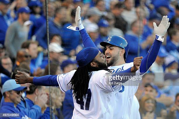 Eric Hosmer of the Kansas City Royals celebrates with Johnny Cueto after scoring off of Josh Fields of the Houston Astros walking Salvador Perez of...