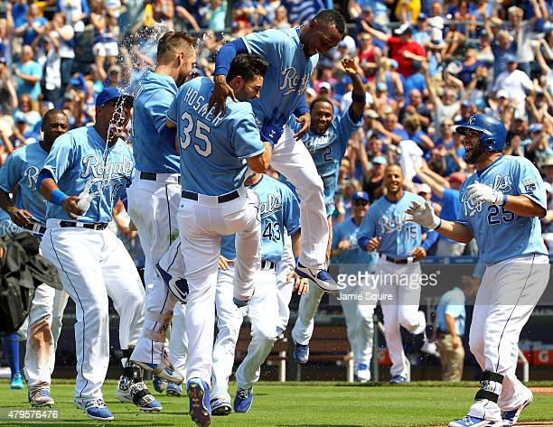 Eric Hosmer of the Kansas City Royals is mobbed by teammates after driving in the gamewinning run in the bottom of the 9th inning against the...