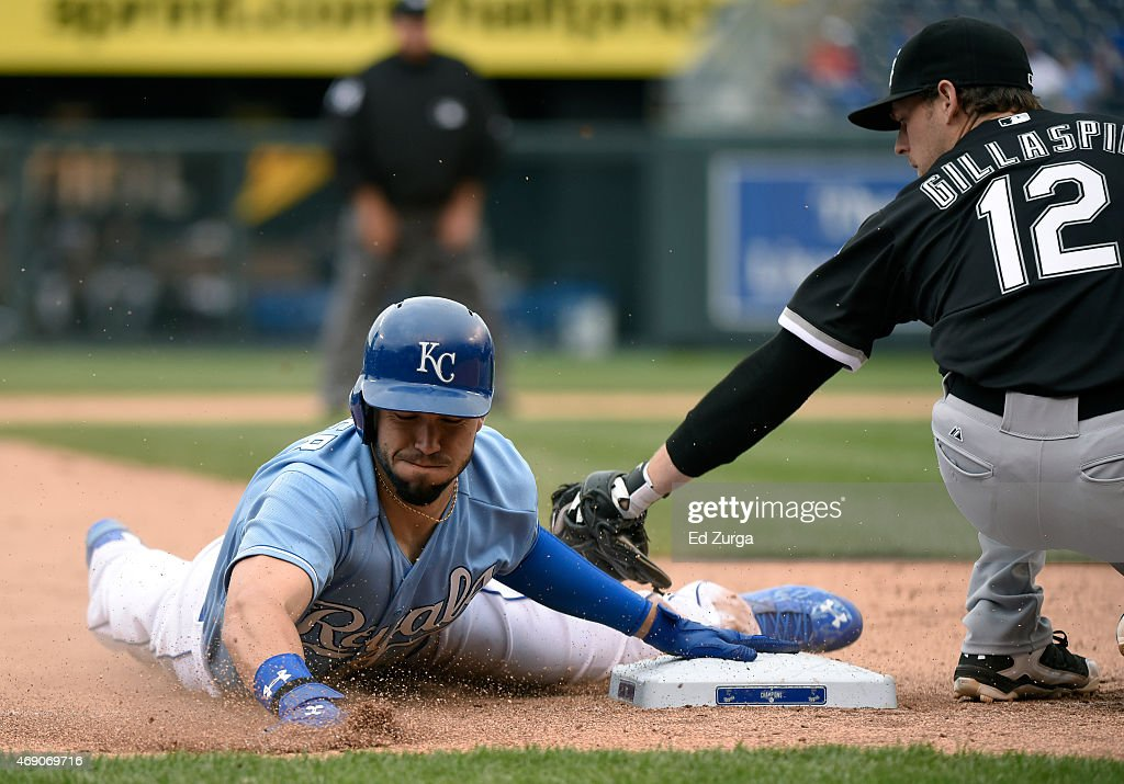 Eric Hosmer #35 of the Kansas City Royals slides into third for a steal past the tag of Conor Gillaspie #12 of the Chicago White Sox in the eighth inning on April 9, 2015 at Kauffman Stadium in Kansas City, Missouri.