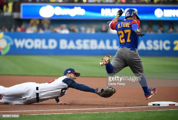 Eric Hosmer of the United States dives but can't make the tag on Jose Altuve of Venezuela on a single during the first inning of the World Baseball...
