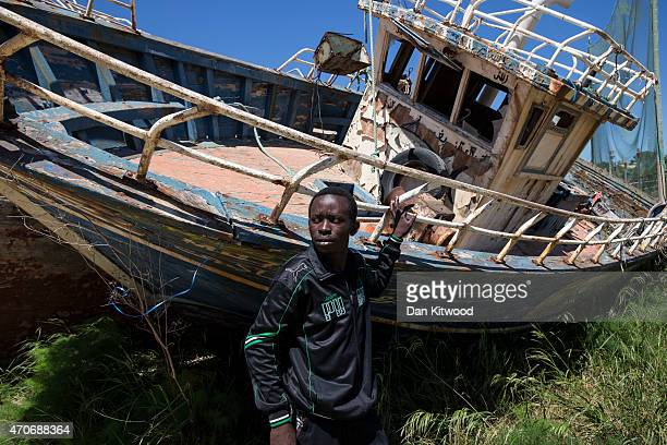 Eric Joseph a migrant from Nigeria stands in a 'boat graveyard' by the port on April 22 2015 in Lampedusa Italy Eric left Libya on a vessel and spent...