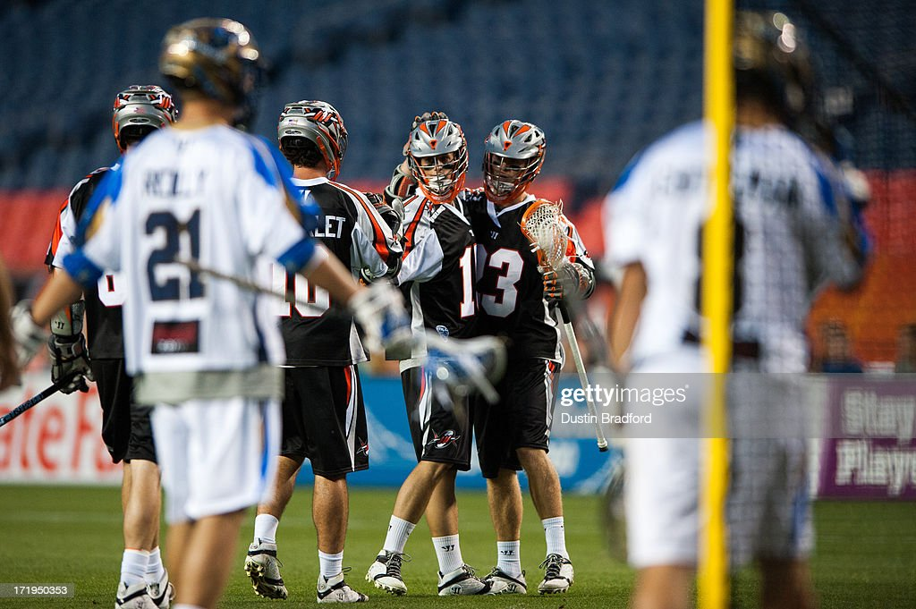 Eric Law #15 of the Denver Outlaws celebrates a goal with Drew Snider #23 during a Major League Lacrosse game against the Charlotte Hounds at Sports Authority Field at Mile High on June 29, 2013 in Denver, Colorado. The Outlaws beat the Hounds 17-11 and improved to 9-0 on the season.