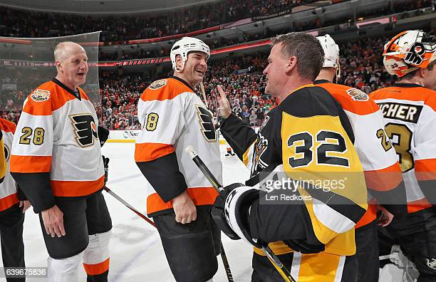 Eric Lindros and Kjell Samuelsson of the Philadelphia Flyers Alumni greet Dave Hannan of the Pittsburgh Penguins Alumni following their game on...