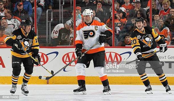 Eric Lindros of the Philadelphia Flyers Alumni skates between Greg Malone and Colby Armstrong of the Pittsburgh Penguins Alumni on January 14 2017 at...