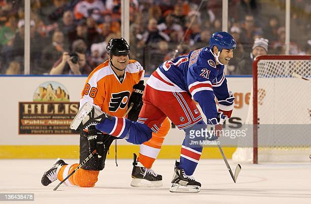 Eric Lindros of the Philadelphia Flyers has a laugh with Mathieu Schnieder of the New York Rangers during the 2012 Bridgestone NHL Winter Classic...