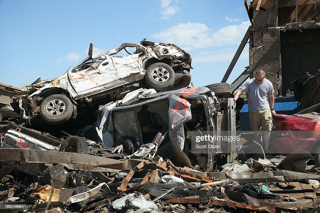 Eric Lowery looks over damage to his mother's vehicle after it was blown from her workplace and came to rest on debris of a collapsed building nearby after a tornado ripped through the area on May 22, 2013 in Moore, Oklahoma. The tornado of at least EF5 strength and two miles wide touched down May 20 killing at least 24 people and leaving behind extensive damage to homes and businesses. U.S. President Barack Obama promised federal aid to supplement state and local recovery efforts.