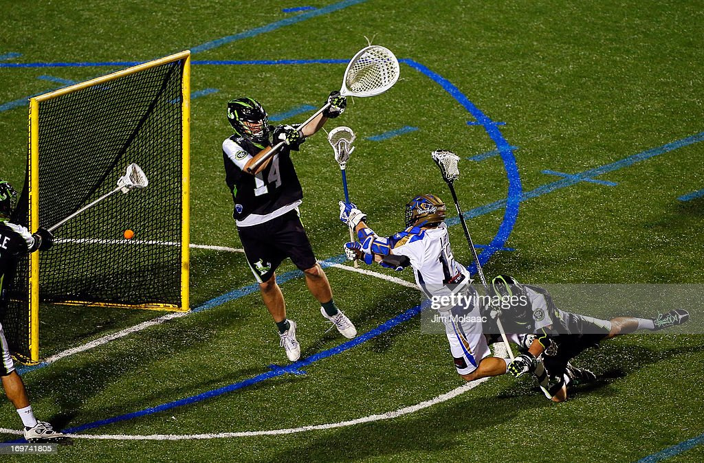 Eric Lusby #12 of the Charlotte Hounds scores the game-winning goal in the fourth quarter past Drew Adams #14 and Michael Skudin #92 of the New York Lizardsduring their Major League Lacrosse game at Shuart Stadium on May 31, 2013 in Uniondale, New York.