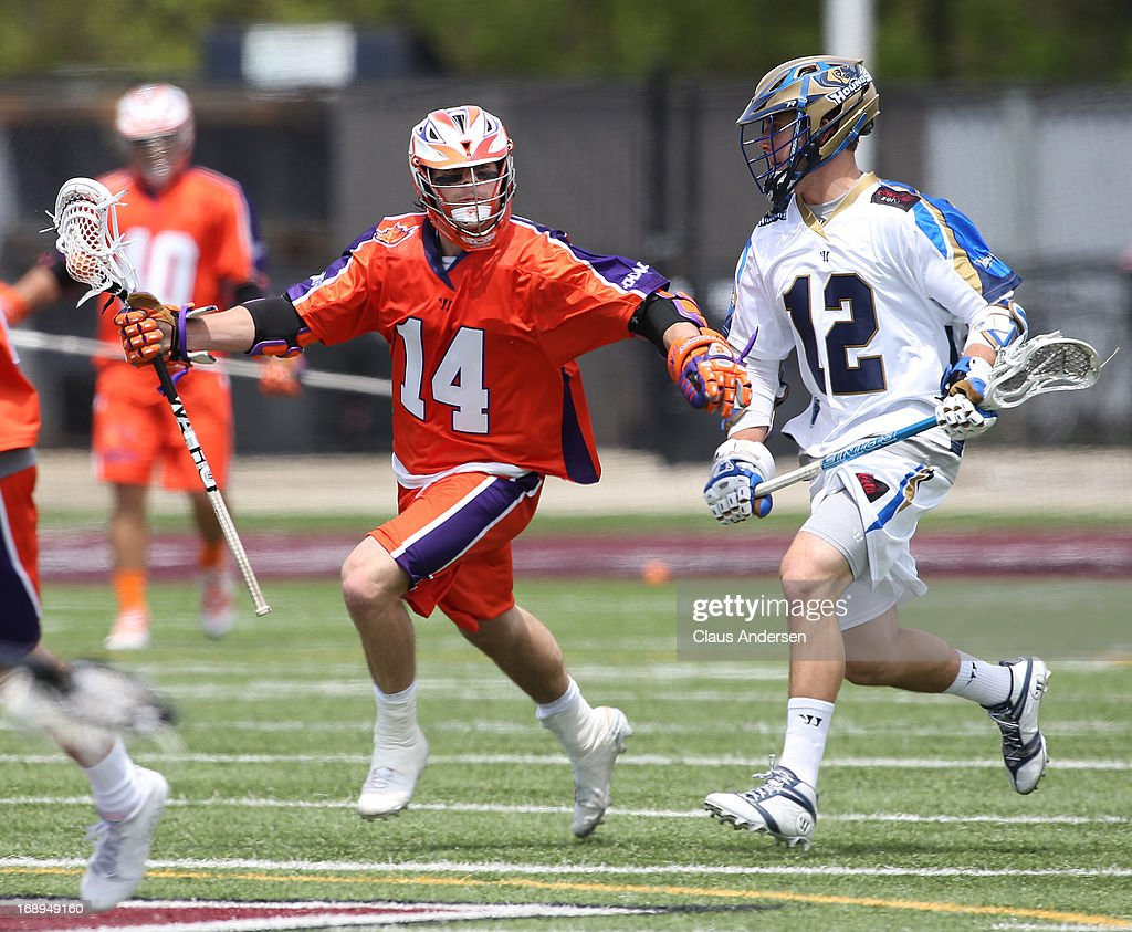 Eric Lusby #12 of the Charlotte Hounds tries to check Cameron Lao-Gosney #14 of the Hamilton Nationals in a Major League Lacrosse game at Ron Joyce Stadium in Hamilton, Ontario, Canada. The Nationals defeated the Hounds 16-15 in overtime.