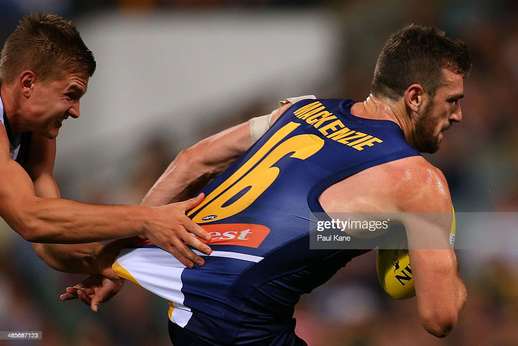Eric Mackenzie of the Eagles looks to break from a tackle by Ollie Wines of the Power during the round five AFL match between the West Coast Eagles and the Port Power at Patersons Stadium on April 19, 2014 in Perth, Australia.