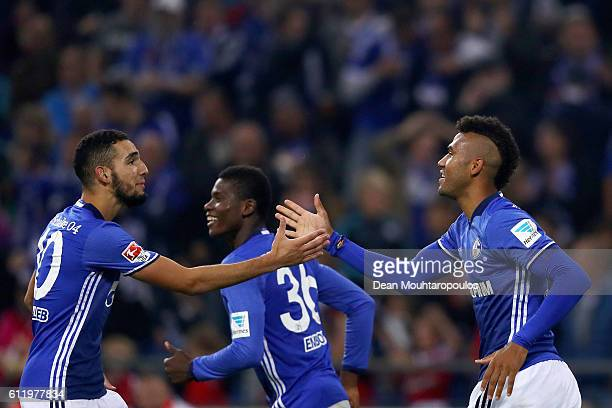 Eric Maxim ChoupoMoting of Schalke celebrates with team mates Nabil Bentaleb and Breel Embolo after he takes and scores a penalty during the...