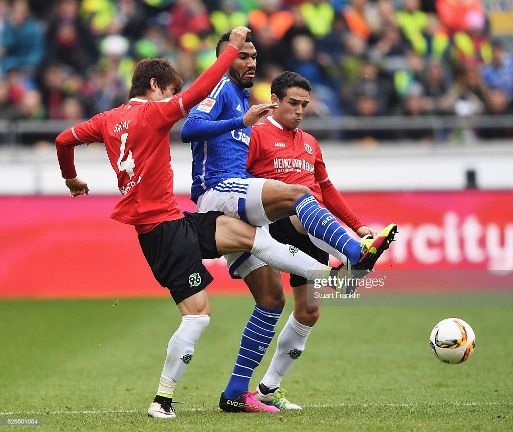 Eric Maxim Choupo-Moting of Schalke is challenged by Hiroki Sakai and Manuel Schmiedebach of Hannover during the Bundesliga match between Hannover 96 and FC Schalke 04 at the HDI Arena on April 30, 2016 in Hanover, Lower Saxony.