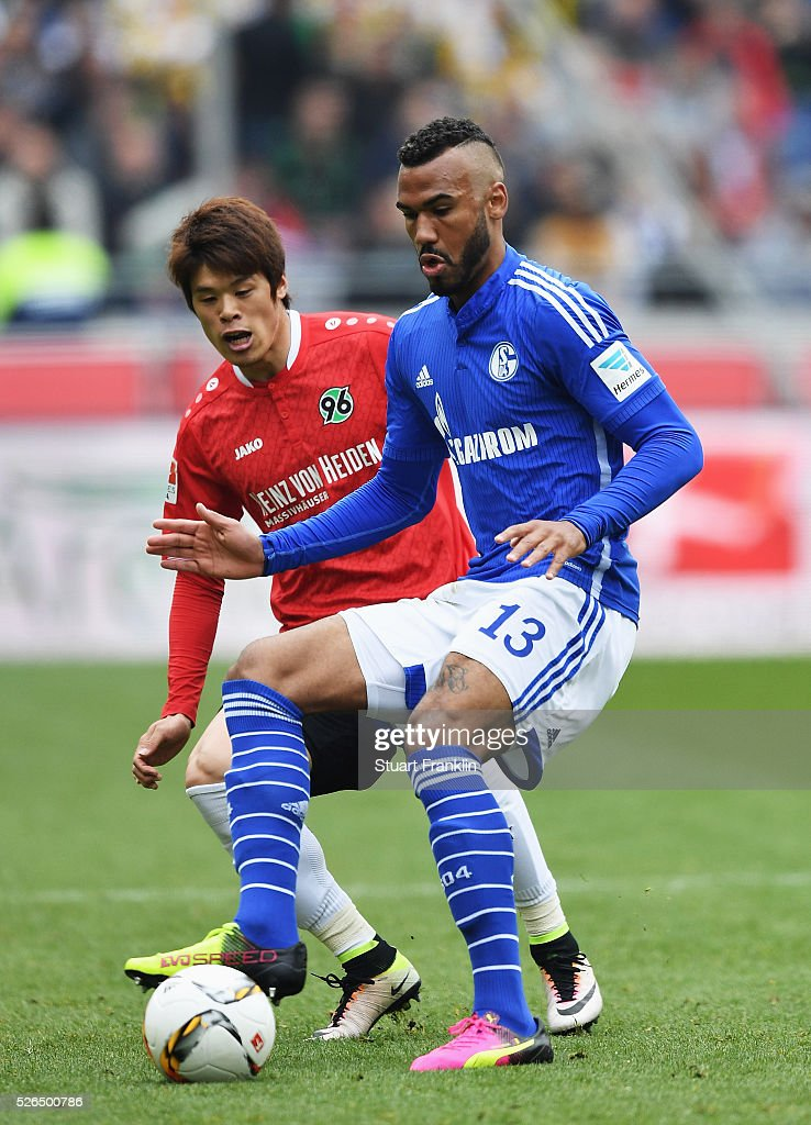 Eric Maxim Choupo-Moting of Schalke is challenged by Hiroki Sakai of Hannover during the Bundesliga match between Hannover 96 and FC Schalke 04 at the HDI Arena on April 30, 2016 in Hanover, Lower Saxony.