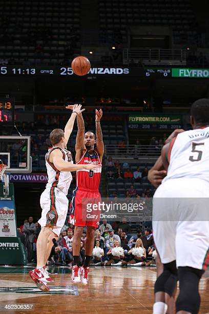 Eric Maynor of the Washington Wizards shoots against Luke Ridnour of the Milwaukee Bucks on November 27 2013 at the BMO Harris Bradley Center in...